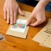 Karten-Kalender – Einblick in die Produktion per Hand – das Bekleben der Verpackung – corpus delicti design Hamburg – Wir machen Geschenke