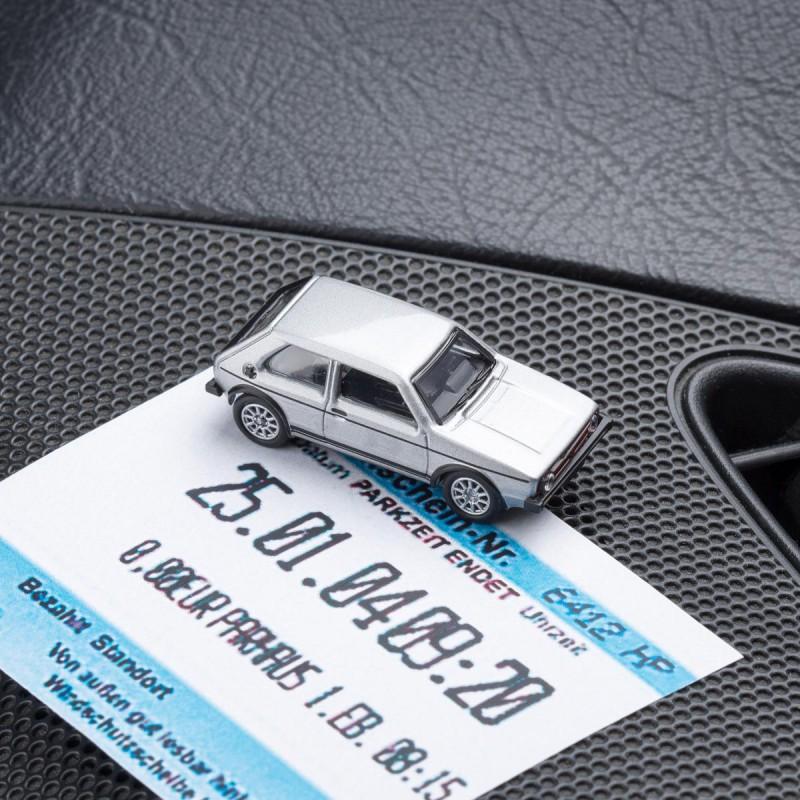 Magnetischer Parkscheinhalter VW Volkswagen Golf GTI I silber mit einem Parkschein auf einem Armaturenbrett – corpus delicti design Hamburg – Wir machen Geschenke